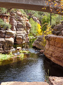 River running under a bridge with Red Rocks in Slide Rock State Park outside Sedona Arizona