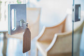 Close up shot of sliding glass door lock, with key chain hanging on the door lock key.