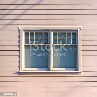 Sliding glass window of a home with white wall. View of a rectangular window with sliding glass panes and white frame on a sunny day. It is on a sunlit wall with white horizontal lap siding.