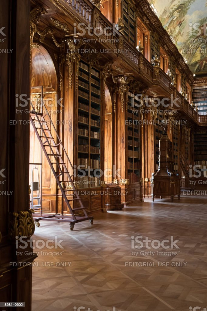 Sliding ladder and elaborately carved bookshelves of the Philosophical Hall at the Library of the Strahov Monastery in Prague. stock photo