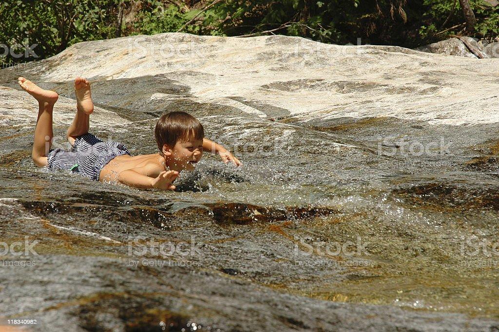 Sliding on a rock stock photo