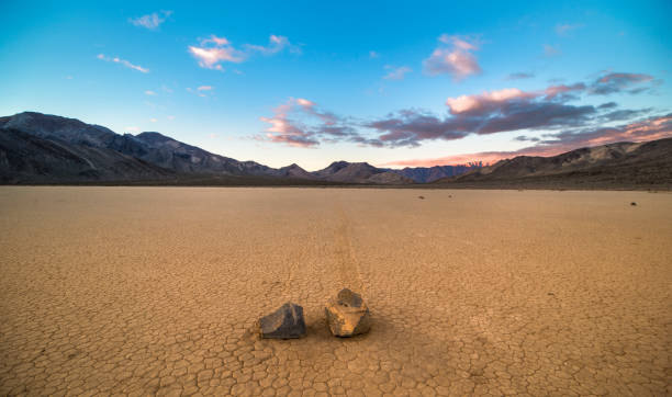 Sliding rock paving a path through the desert - Death Valley National Park, Racetrack Playa, Desert, Motion, California lake bed stock pictures, royalty-free photos & images