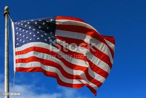 Slight motion American flag against a blue sky with clouds