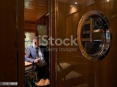 A view through a slightly ajar door and a senior wine aficionado savoring some wine in the cruise ship wine closet.