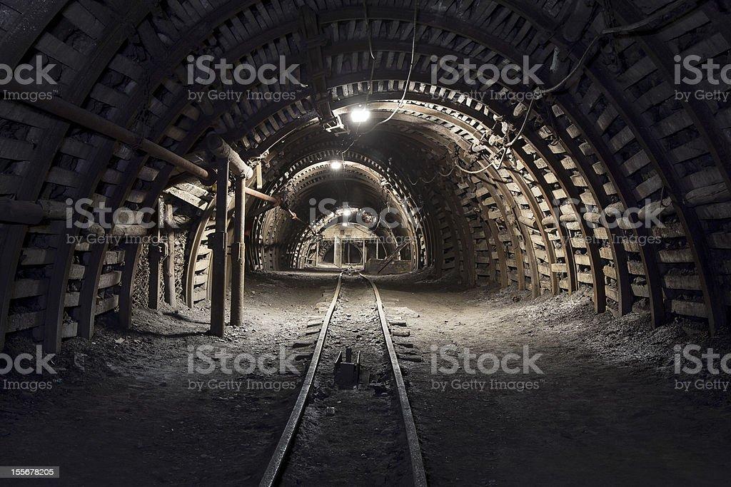 Slightly lit underground tunnel in the coal mine stock photo