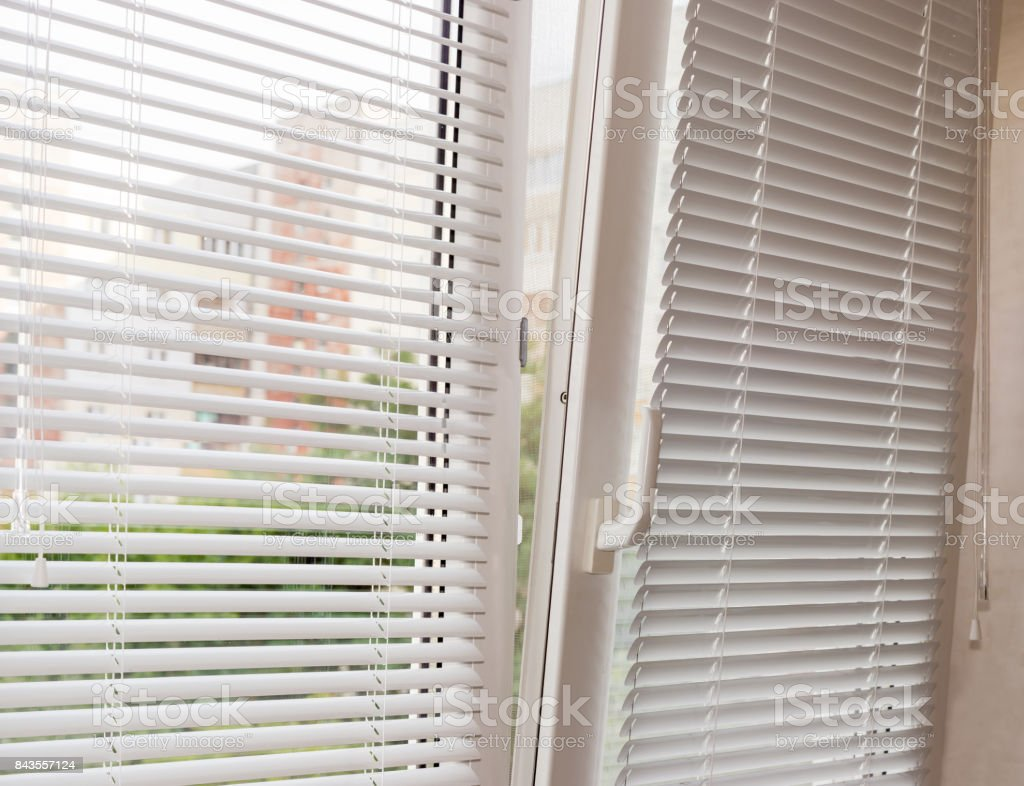 Slightly open modern plastic window with Venetian blinds stock photo