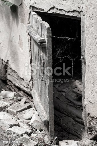 Slightly opened old weathered wooden door and spider web on a darkness background. Scaring background