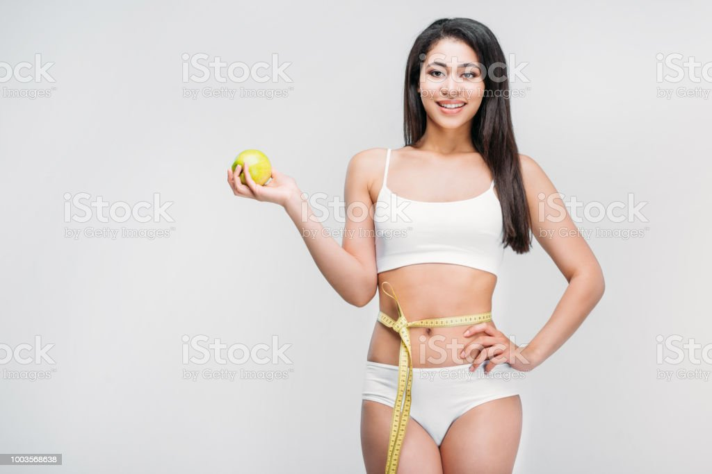 4059e5bba8862 Slim african american girl in white lingerie with measuring tape on waist  holding apple, isolated on grey, diet concept - Stock image .