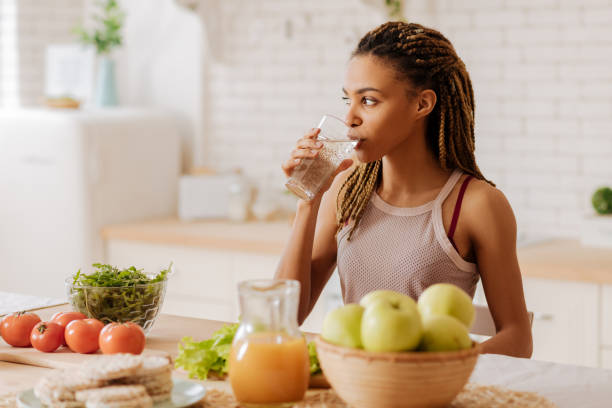 Slim and fit woman drinking water before having breakfast stock photo