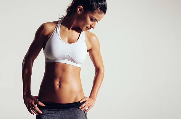 près du corps et la santé féminine en studio de modèle - brassière de sport photos et images de collection