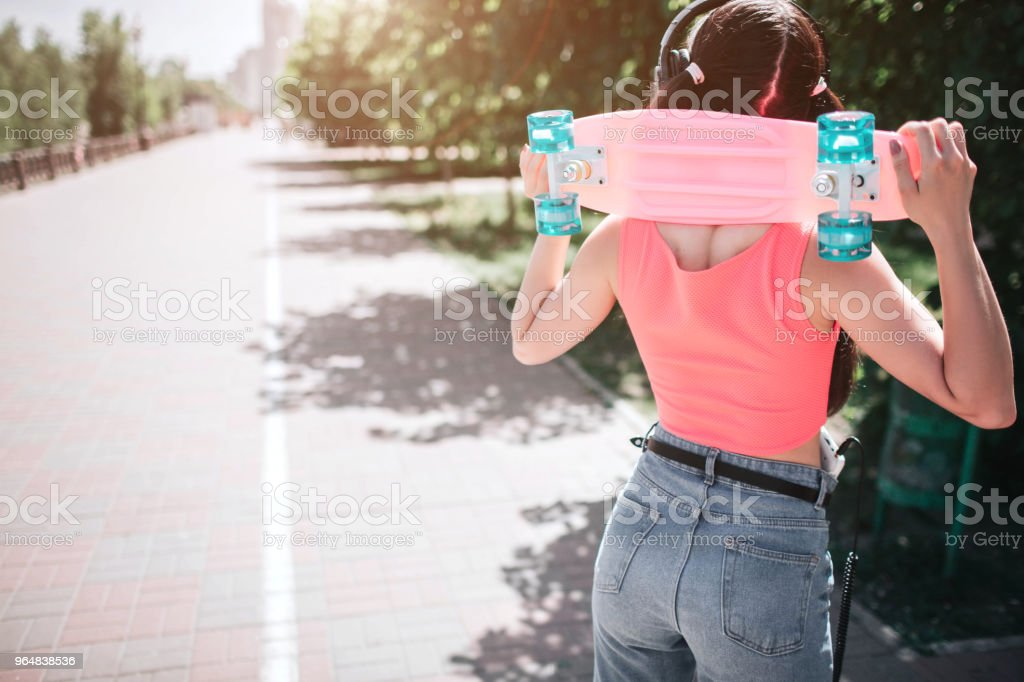Slim and well-built melomaniac girl is posing. She is standing back to camera and holding skate on the neck. She has headphones on her head royalty-free stock photo