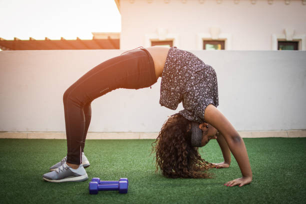 Slim attractive African-ameican young woman in sportswear exercising in Urdhva Dhanurasana pose at rooftop gym. stock photo