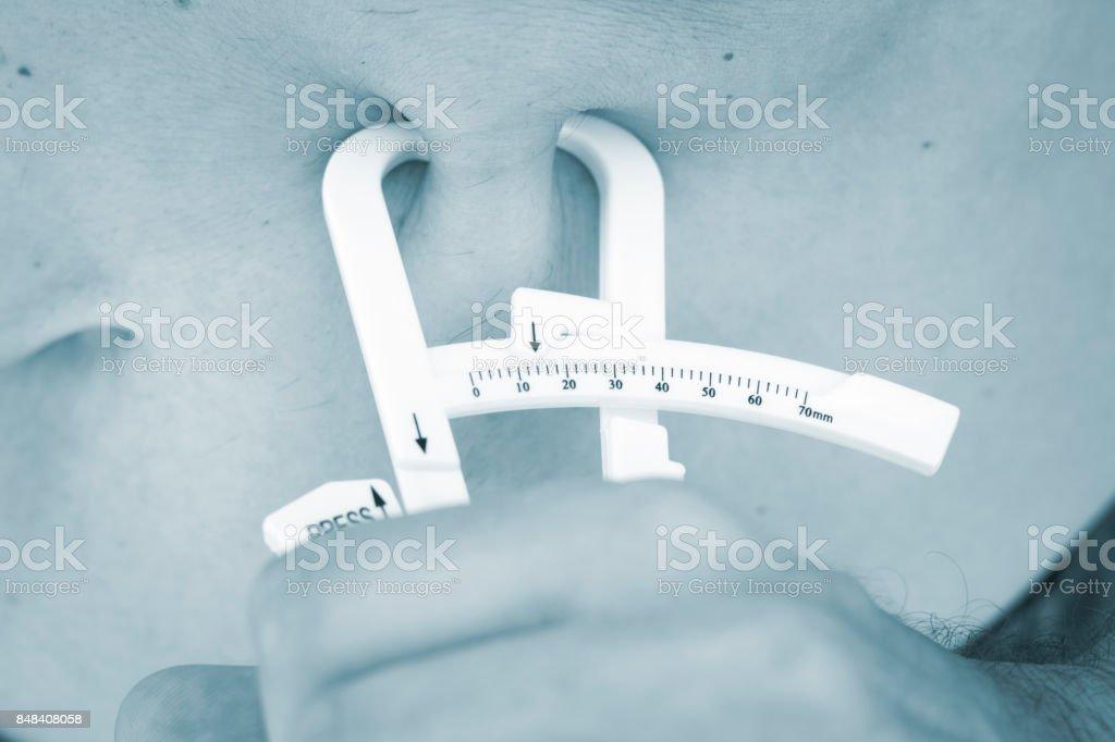 Magro jovem atraente usando fita métrica para perda de peso de medida e muscular na perna. - foto de acervo