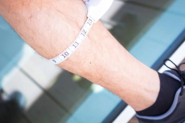schlanke attraktive junge mann mit maßband maßnahme gewichtsverlust und muskelaufbau am bein. - schlanke waden stock-fotos und bilder