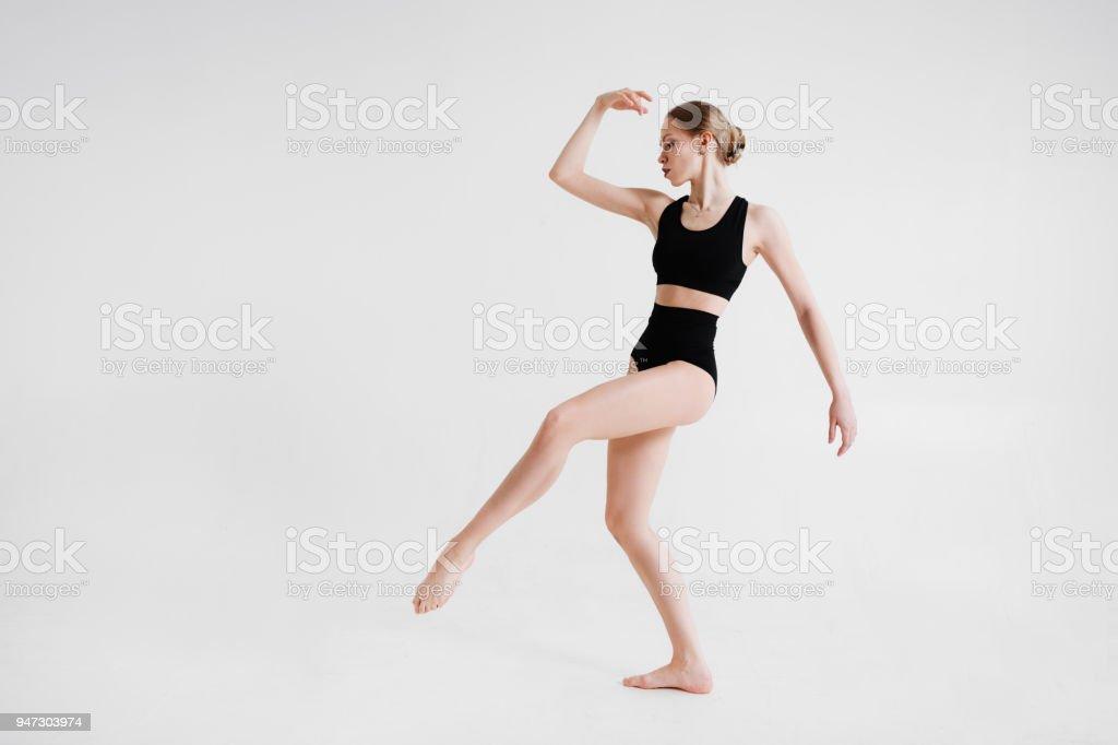 Slim ballerina in a black sport underwear is posing on a white...