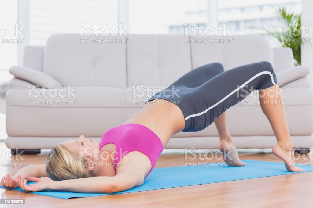 Slim blonde lifting her pelvis on exercise mat stock photo