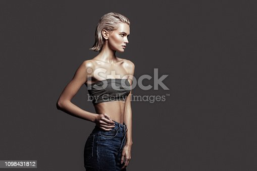 Model with bob. Slim blonde-haired model with bob cut wearing nice jeans and open shoulder top