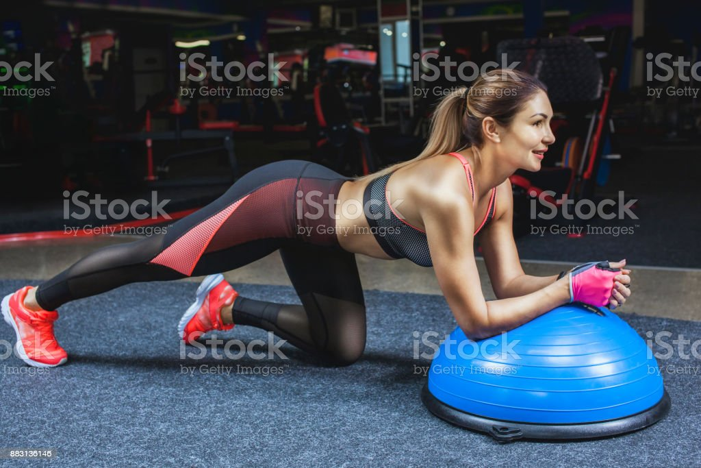 Slim, bodybuilder girl, does the exercises with Ball Balance in the gym. stock photo