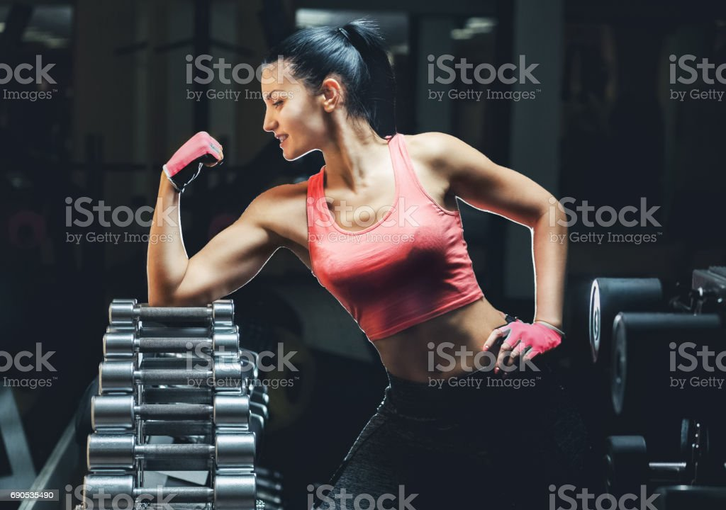 Slim bodybuilder girl shows biceps while training in the gym. Sports concept fat burning stock photo