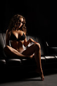 Slim brunette with long locks in sexy undewear sitting on a black leather sofa in the dark room shot