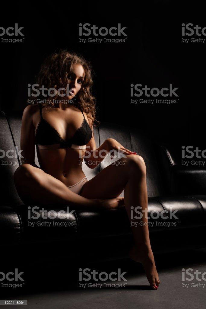 Schlanke Brünette in Undewear auf Sofa im Dunkeln – Foto
