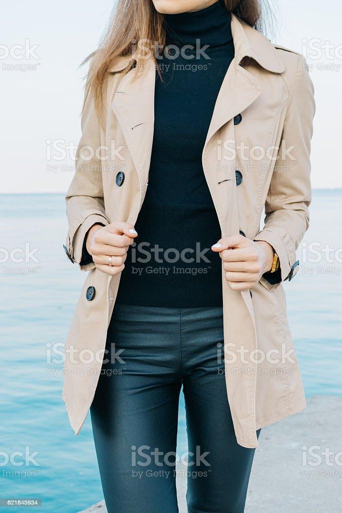 Slim elegant girl in a beige coat and black pants stock photo