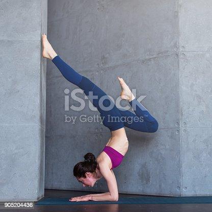 istock Slim female yogi wearing sportswear performing inversion or arm balance standing upside down on forearms 905204436