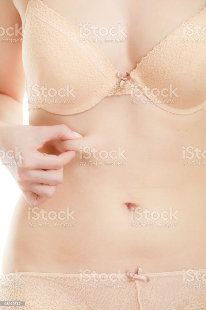 Slim fit girl pinching her belly fat. 免版稅 stock photo