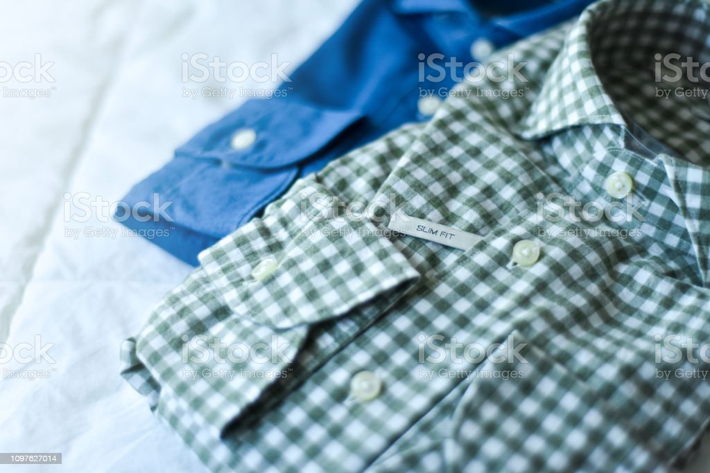Modern styled men\'s button down shirts folded on a bed