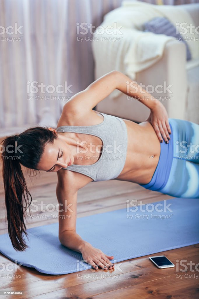 Slim fitness young woman doing side plank exercise at home with smartphone photo libre de droits