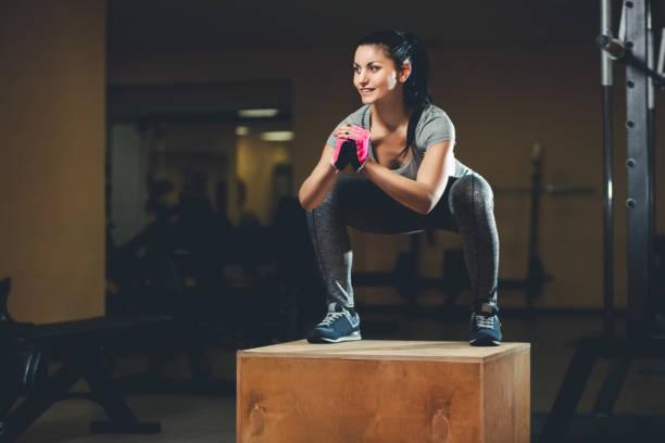 schlankes girl bodybuilder springen auf einem hölzernen kasten vor dem spiegel während des trainings in der turnhalle - damen leggings übergrößen stock-fotos und bilder