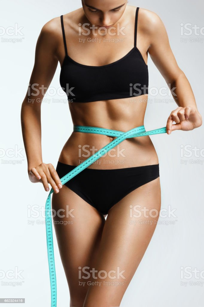 Slim girl in black lingerie with a ribbon measures the size of the waist stock photo