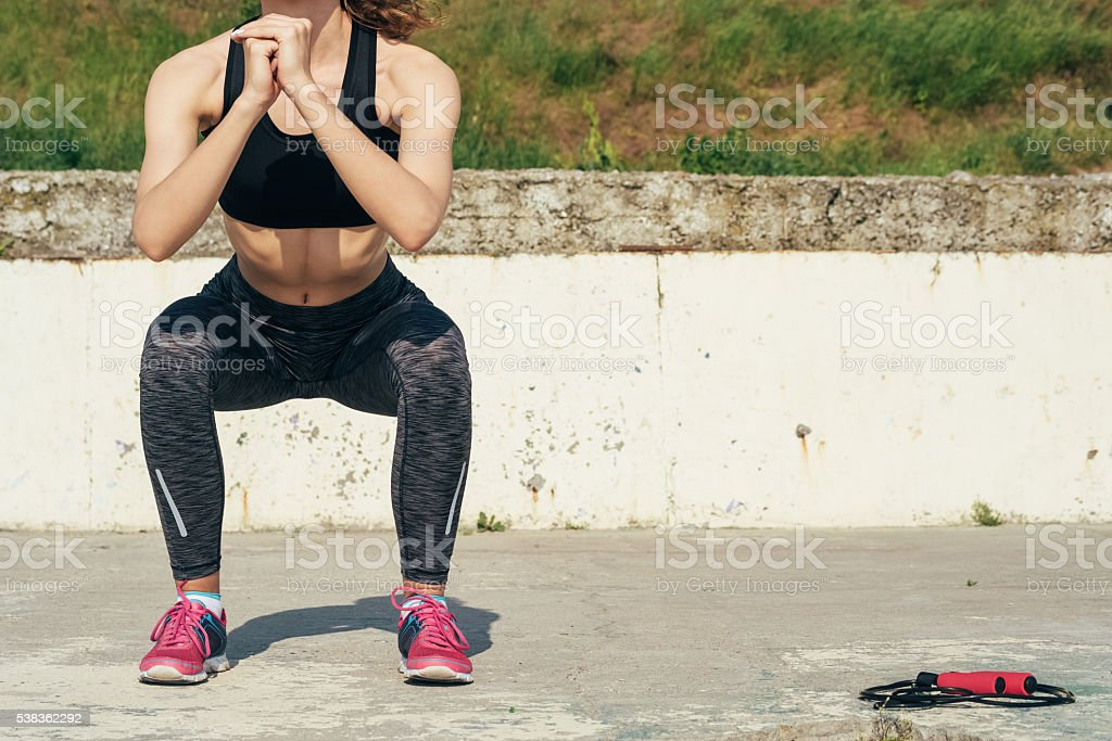 Slim girl in sportswear doing sit-ups outdoors in the morning stock photo