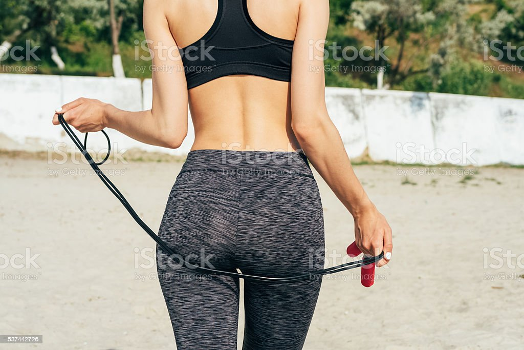 Slim girl in sportswear on the beach stock photo