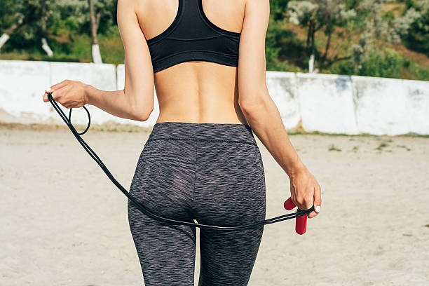 slim girl in sportswear on the beach - buttock stock photos and pictures