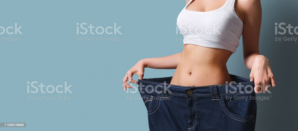 Slim girl in too big pants. Weight loss - Foto stock royalty-free di Abbigliamento