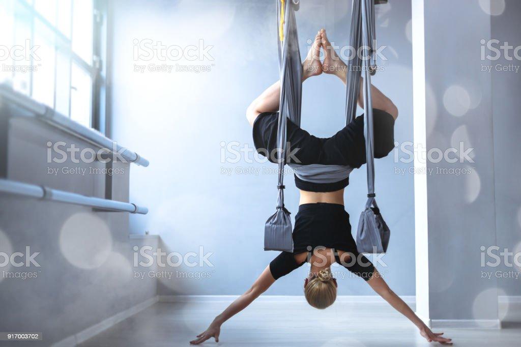 Slim girl practising air-yoga stock photo