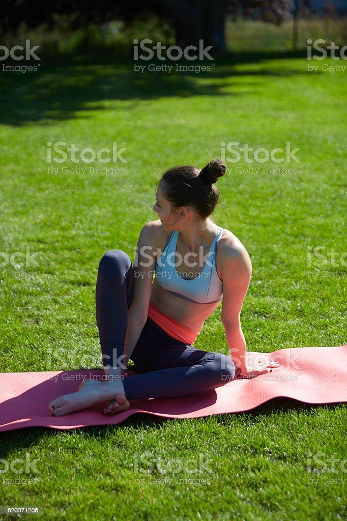 Slim girl stretching in park on mat zbiór zdjęć royalty-free