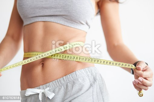 istock Slim girl with centimeter on white 610752618