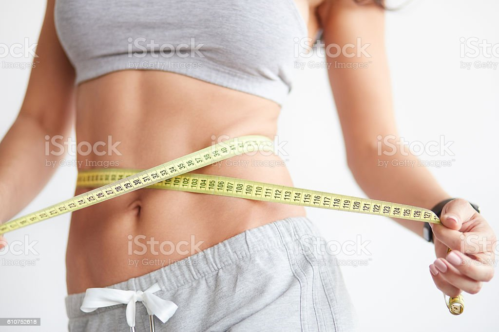 Slim girl with centimeter on white stock photo