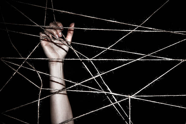 Slim hand behind the interlaced ropes stock photo