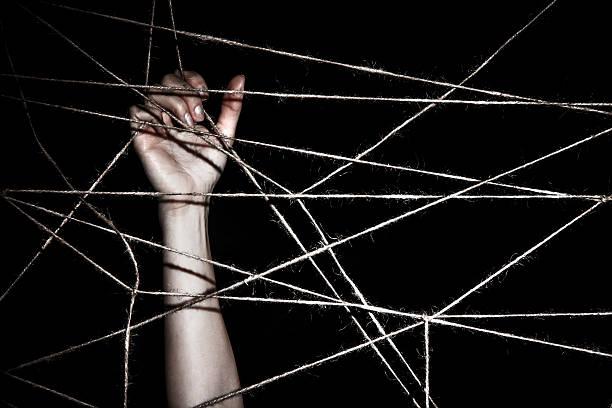 slim hand behind the interlaced ropes - leinenhosen frauen stock-fotos und bilder