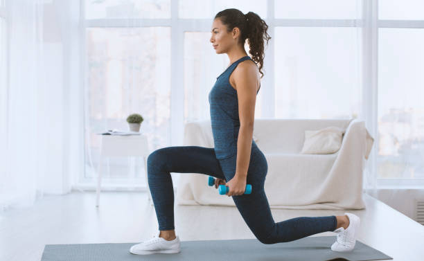 slim hispanic girl doing lunges with dumbbells at home, empty space - fitness imagens e fotografias de stock
