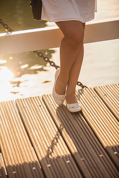 slim legs in ballet flats on wooden bridge - flat shoe stock photos and pictures