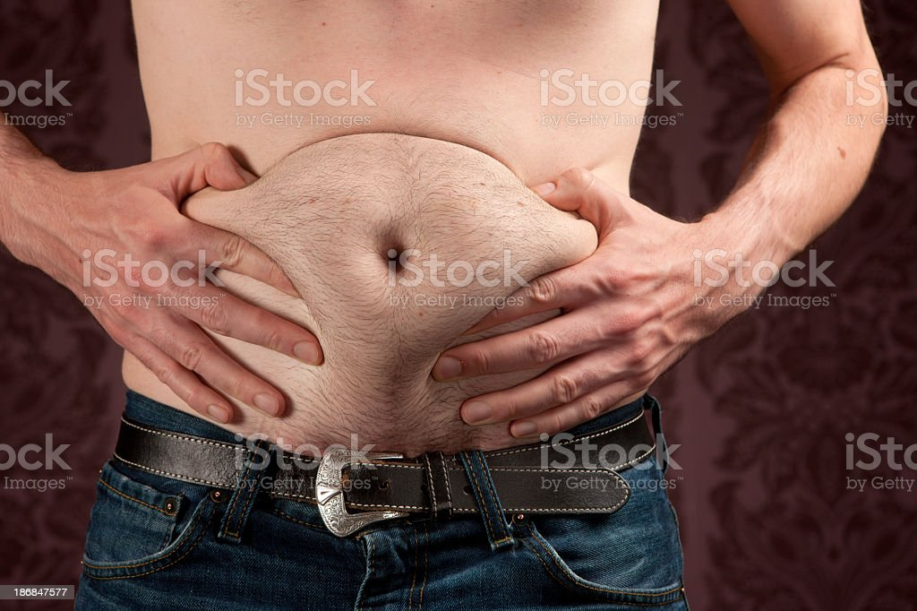 Slim man holding his fat beer belly on dark background