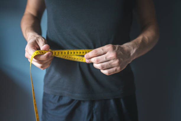Slim man measuring his waist. Healthy lifestyle, body slimming, weight loss concept. Dieting, Healthy Eating, Men, Overweight, Measuring Tape dieting stock pictures, royalty-free photos & images