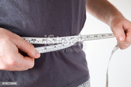 1184112328 istock photo Slim man measuring his waist. Healthy lifestyle, body slimming, weight loss concept. Cares about body. 929029958