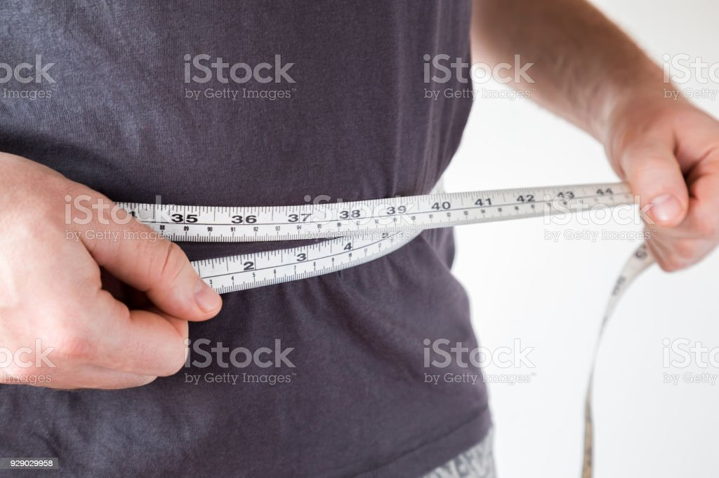 Slim man measuring his waist. Healthy lifestyle, body slimming, weight loss concept. Cares about body. stock photo