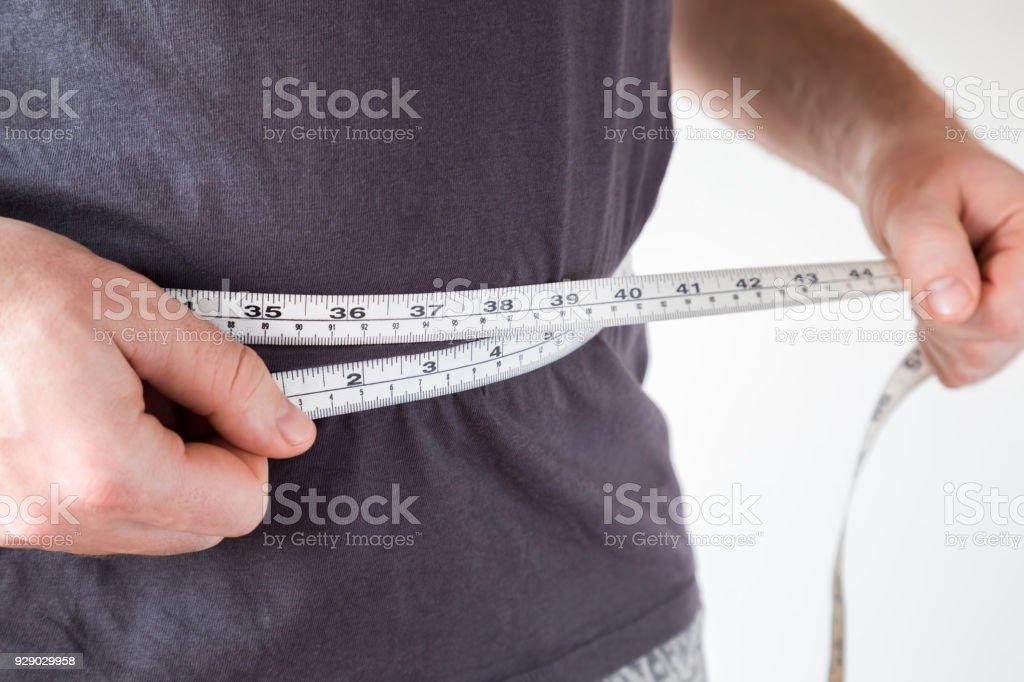 Hombre delgado midiendo su cintura. Estilo de vida saludable, cuerpo que adelgaza, concepto de pérdida de peso. Se preocupa por el cuerpo. - foto de stock