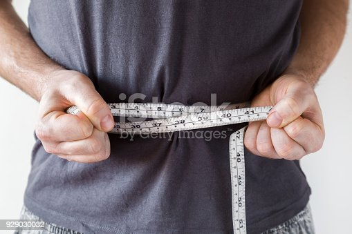 1184112328 istock photo Slim man measuring his waist. Healthy lifestyle, body slimming, weight loss concept. Cares about body. 929030032